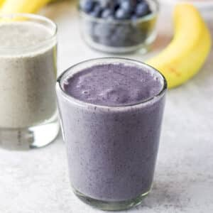Glasses filled with blueberry banana spinach smoothie - square