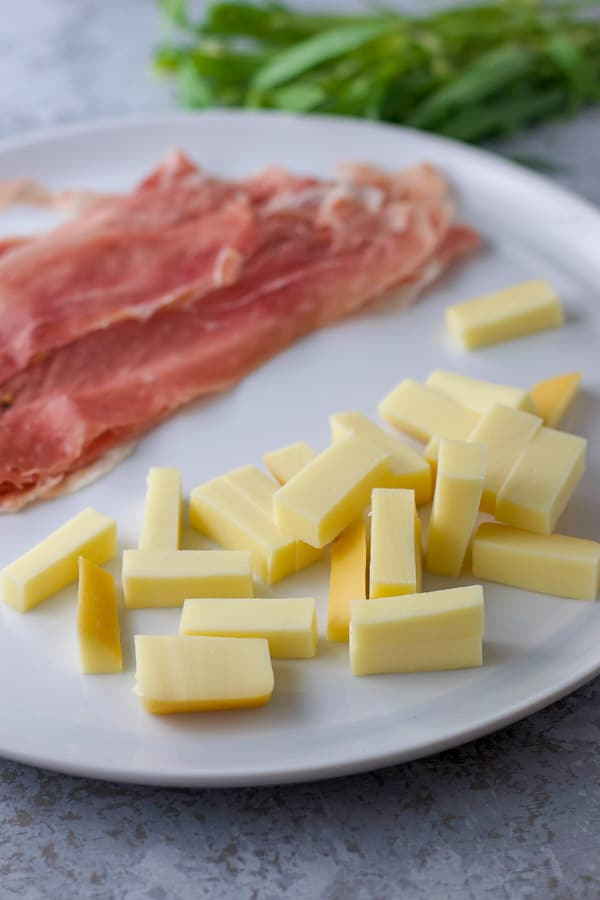 Gouda slices and prosciutto and tarragon in the background for the chicken saltimbocca