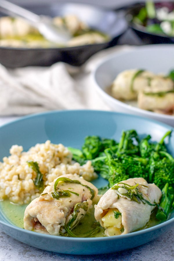 A couple of chicken saltimbocca on a plate with rice and broccoli rabe. There is the pan of chicken saltimbocca in the background - for the chicken saltimbocca recipe