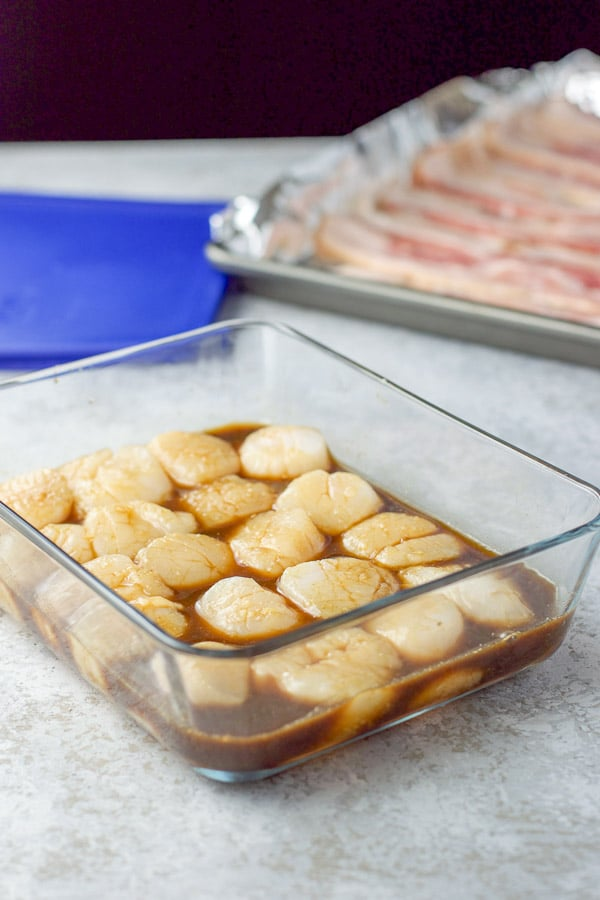 Scallops marinating and bacon on a foil lined pan ready to be cooked for the marinated bacon wrapped scallops