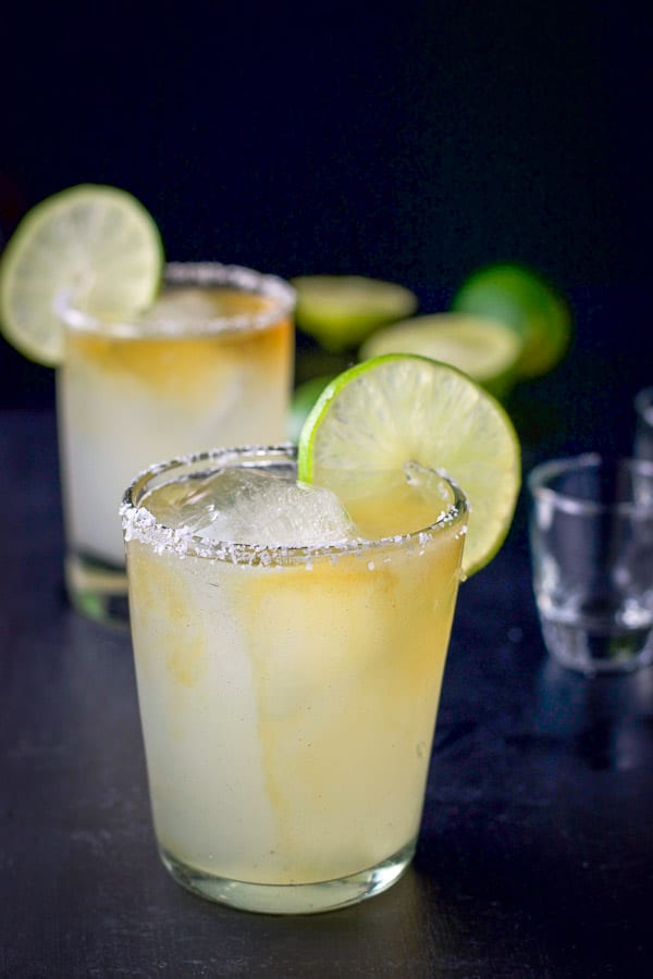 Grand Marnier poured in both margaritas with limes on the rims and in the background