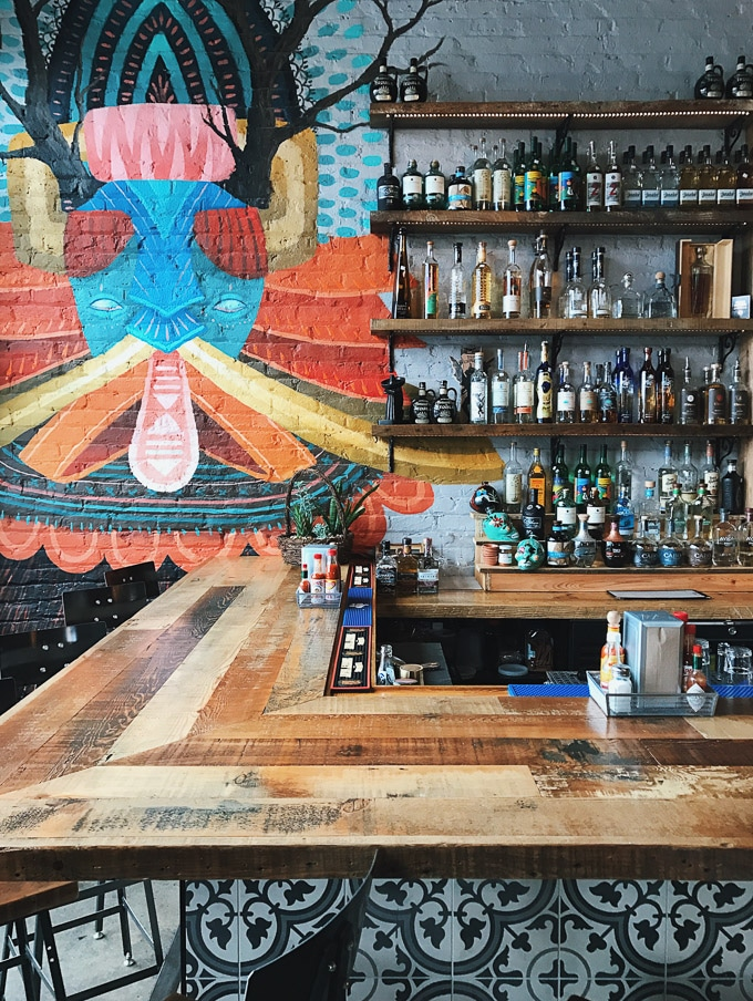 Half of a bar with bottles on shelves and a colorful painting on the wall