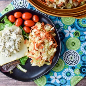 A black plate with slaw, tomatoes, lettuce and chicken salad - square