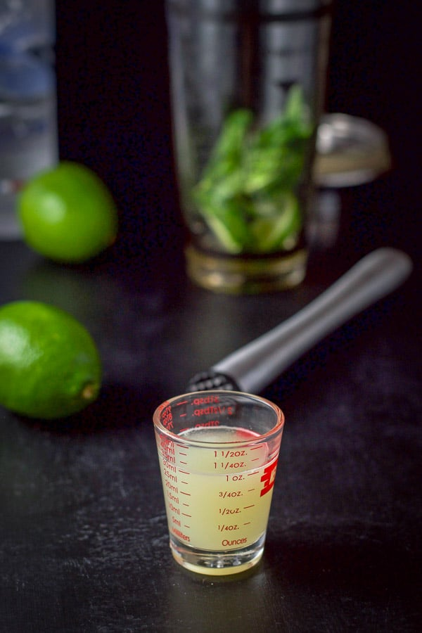 Lime juice poured out with limes in the background and mint in a cocktail shaker