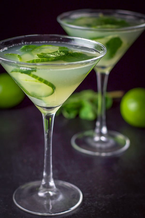 Two cucumber martinis poured out with some limes and mint in the background