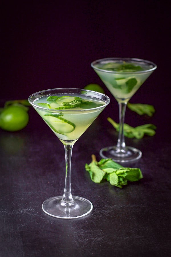Bright photo of two cucumber martinis with mint and limes in the background