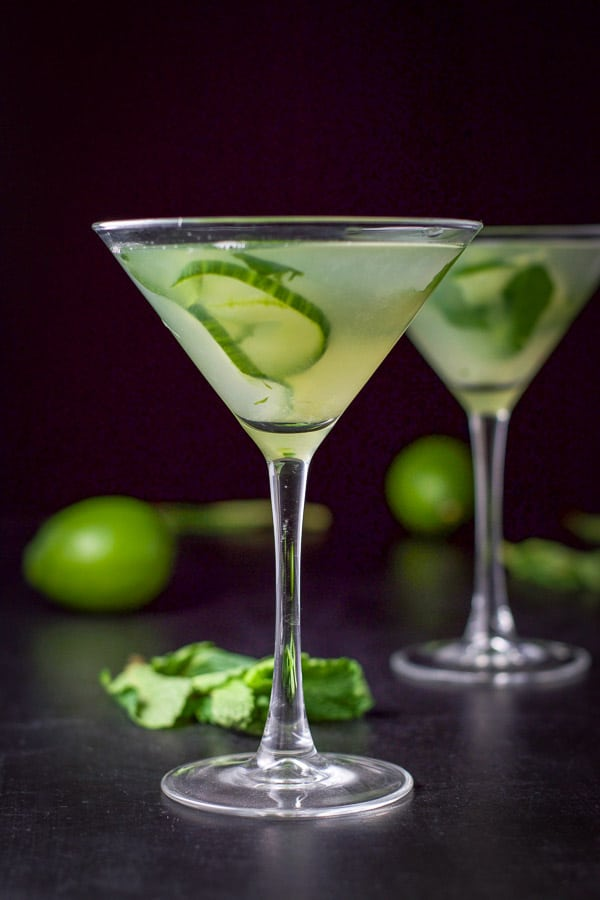 Vertical view of the cucumber martini with two limes and a bunch of mint on the table