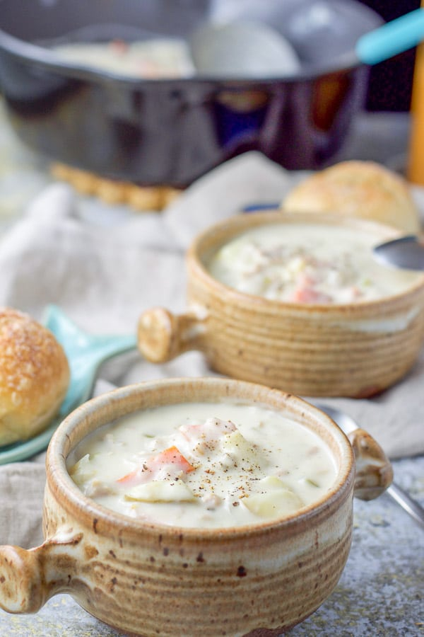 Two crocks of thick chowder with fresh ground pepper on top and rolls in the background