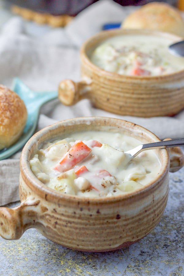 Spoon is in the crock of creamy veggie filled chowder