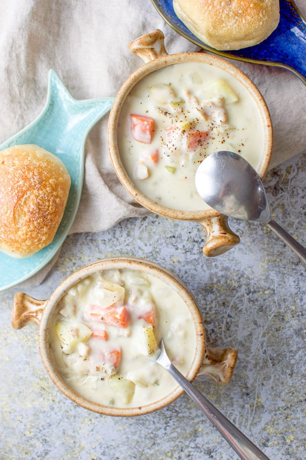 Overhead shot of the clam chowder with the spoons in the crocks and rolls on plates