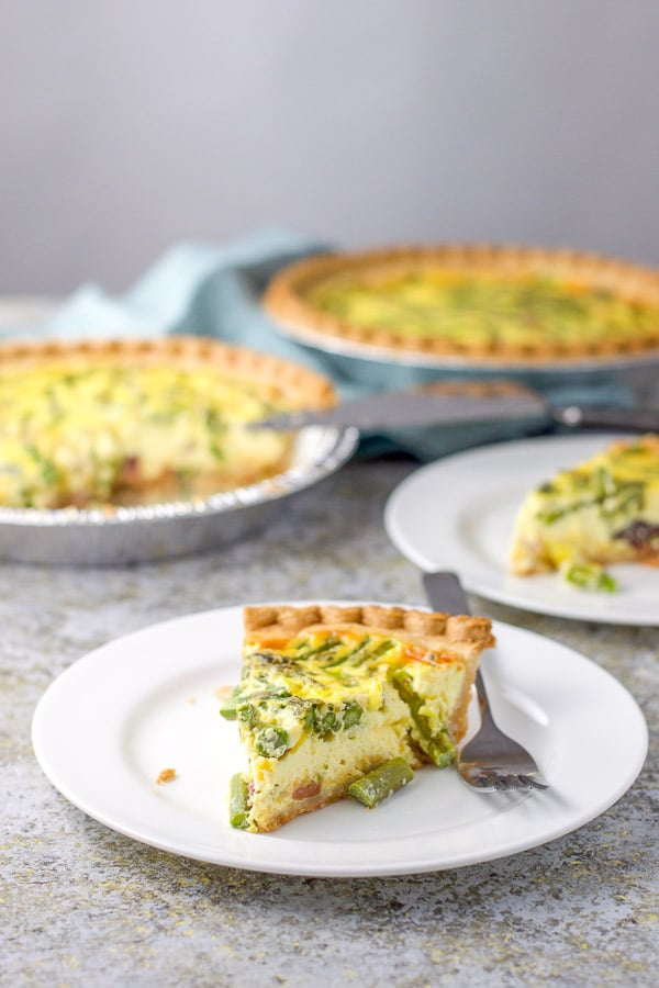 Slices of ham and asparagus quiche on plates with the quiches in the background