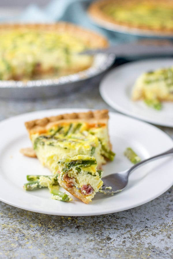 The fork with a piece of quiche on the front of the plate with the two quiches in the background