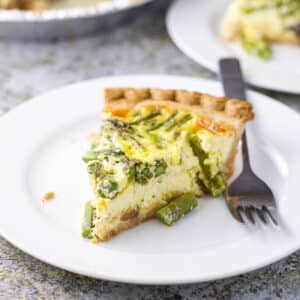 A white plate with a big slice of quiche on it - square