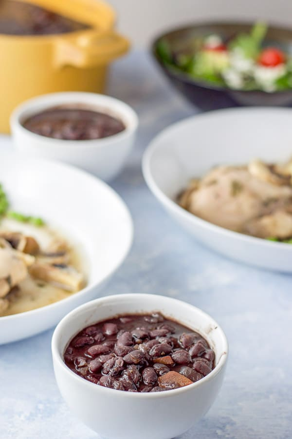 A little bowl of instant pot black beans in front with some plates of chicken and a salad in the background