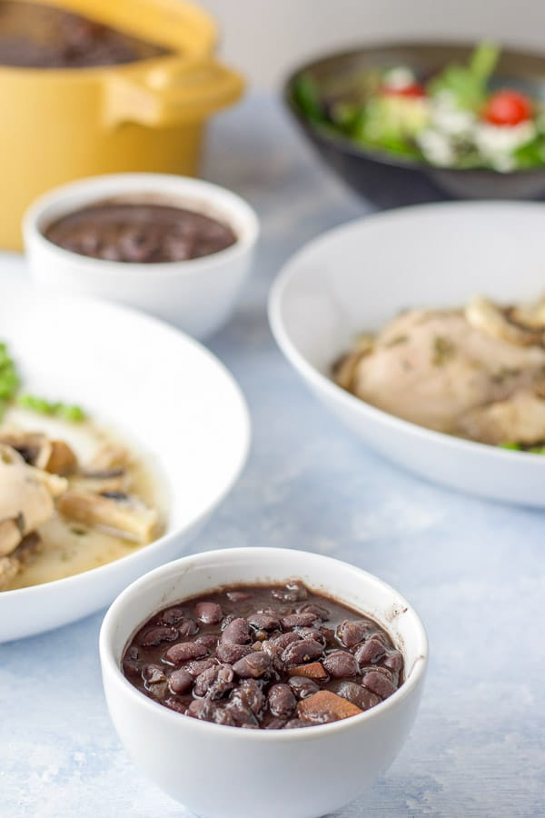 Black beans in a small white bowl with a few plates of chicken and the casserole dish in the background
