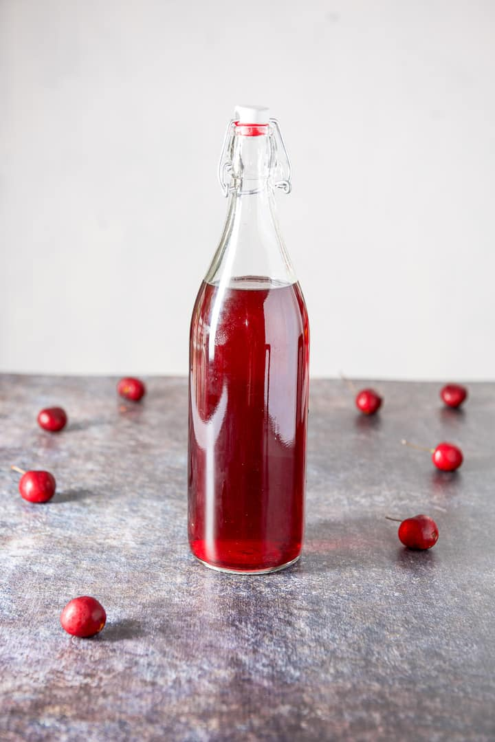 A bottle of cherry vodka on a cookie sheet background with cherries strewn on it