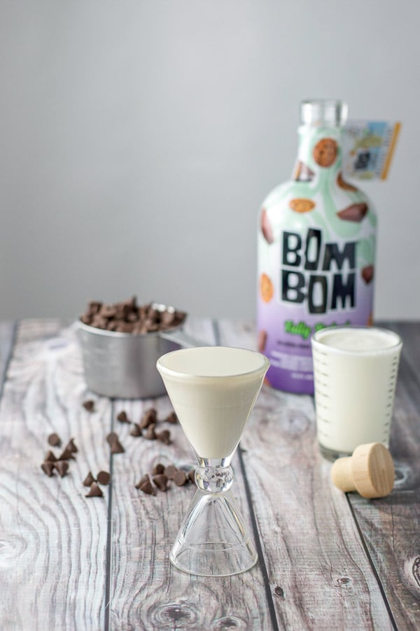 Bom Bom liqueur poured out along with the heavy cream, and chocolate chips in the background with the bottle of liquor
