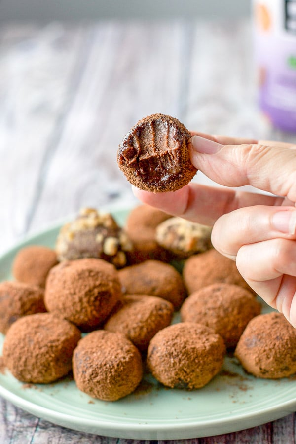A hand holding a truffle with a bite taken out of it, all gooey and delicious