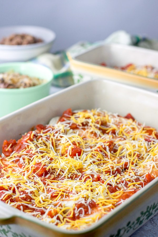 Cheese sprinkled on the enchiladas that are in a baking dish with another baking dish and beef in the background