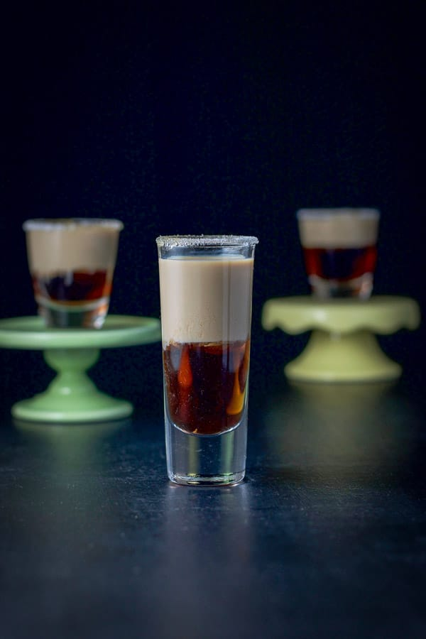 Tall glass of donut shot in front with two short glasses on little pedestals