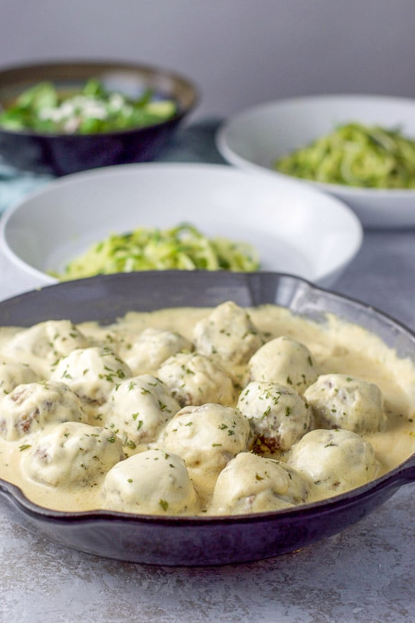 Pan of Swedish meatballs with sour cream sauce front and center with two plates of zoodles in the background