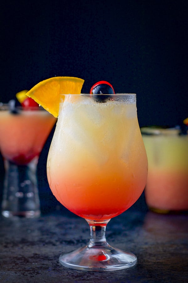 Vertical view of the tulip glass in front filled with the tequila sunrise