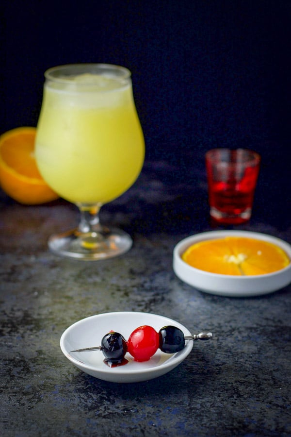 Cherries on a skewer and an orange slice in a small white plate and a shot glass of grenadine and a glass with the cocktail