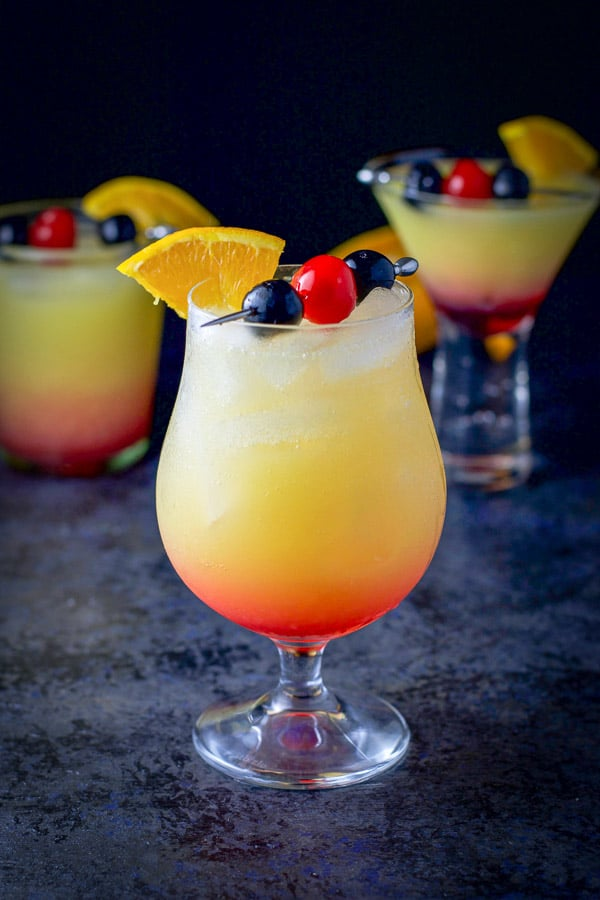 A tulip glass is in front of two other glasses filled with the tequila sunrise