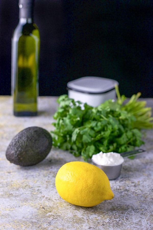 Lemon, yogurt, avocado, cilantro and avocado oil on a table