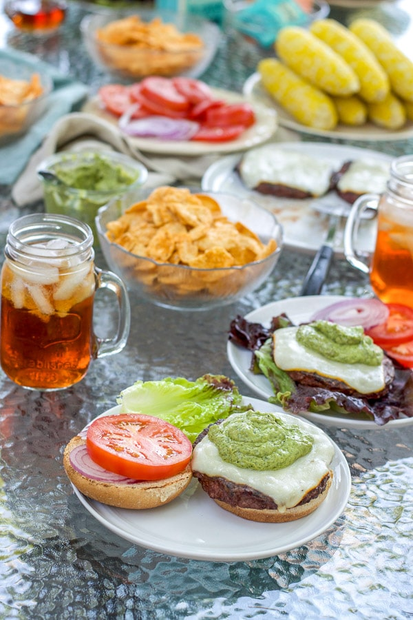 Green dressing on the burgers with a bun, tomato and lettuce and all the summer fare in the background