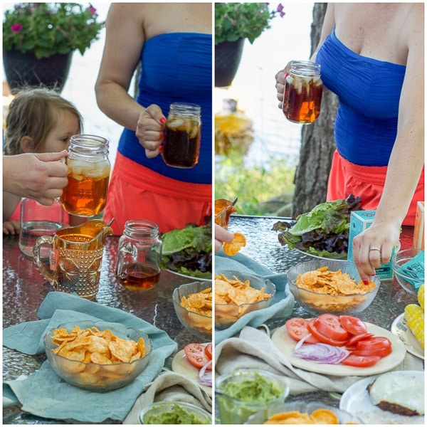 Iced tea in the hands of women and chips in their hands for outside at a lake
