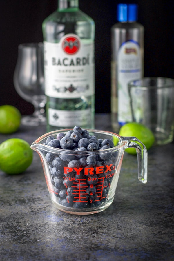 Blueberries, lime, rum and simple syrup on the table along with some glasses