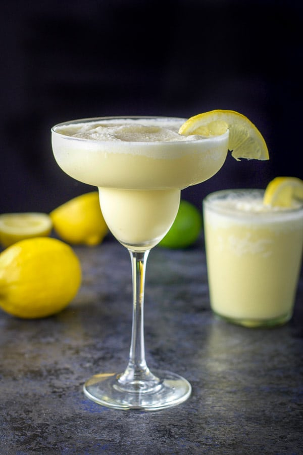Classic tall margarita glass filled with lemon margarita, short glass with margarita in back, surrounded by lemons and a lime