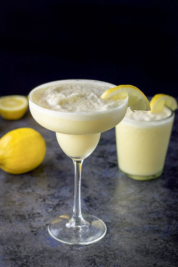 Aerial view of the lemon margarita in a classic margarita glass in front and in an old-fashioned glass in back, next to two lemons