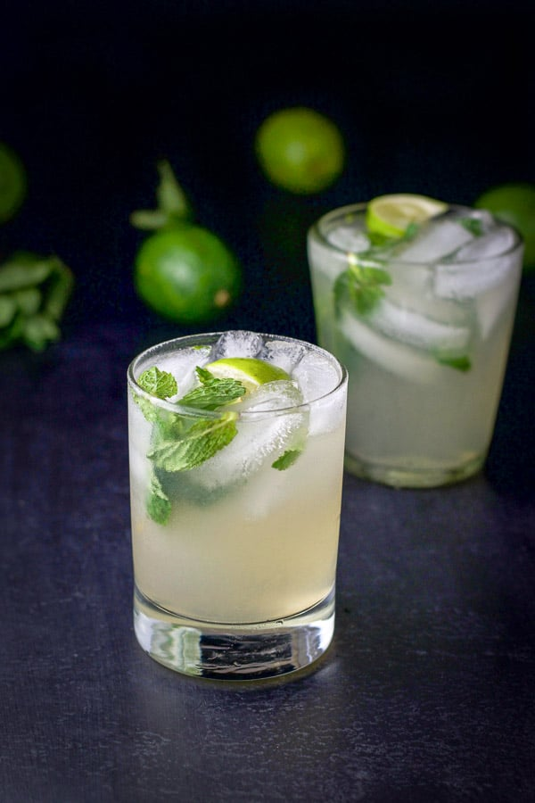 Two glasses of the mojito with limes and mint in the background