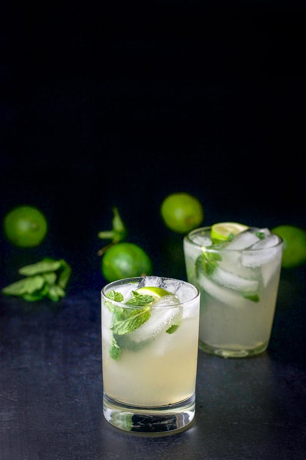 Two double old fashioned glasses filled with the mojito with a bunch of limes and mint leaves in the background