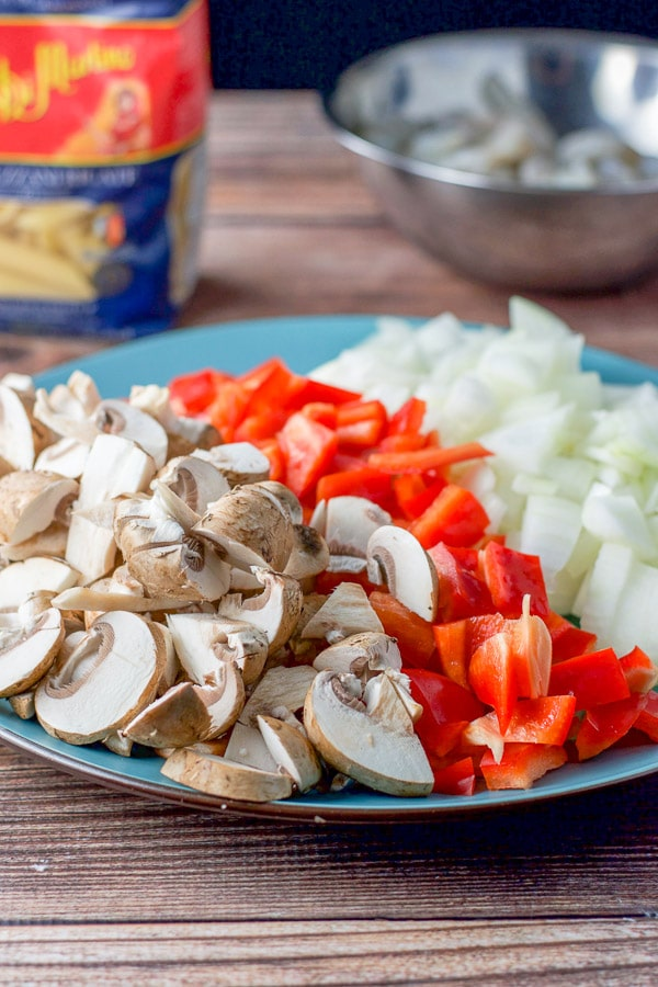 Platter with three rows of chopped vegetables, from left to right: white mushrooms, red bell peppers and onions, with a package of penne pasta and a stainless steel bowl of raw shrimp in the background.