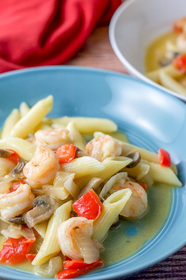 Close up of a bowl of shrimp scampi with penne pasta