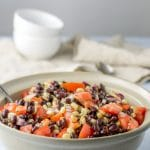 Big serving bowl of black bean salad with two white bowls on a beige napkin in the background