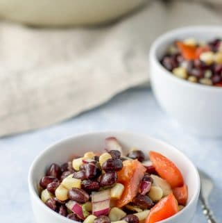 Close up of the two white bowls of bean salad and the big bowl behind them