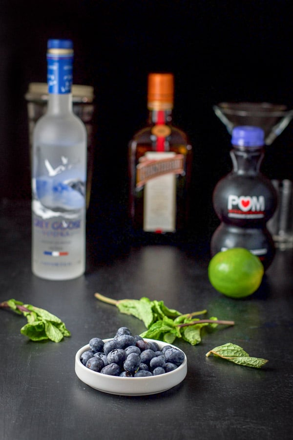 Blueberries, mint leaves, vodka, Cointreau, lime, blueberry juice on a black table