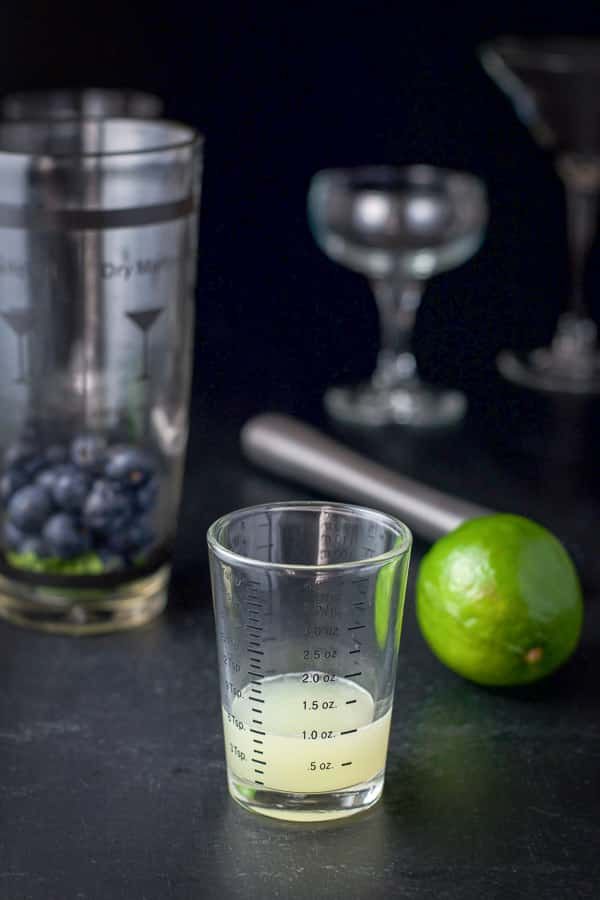 Lime juice measured out with the shaker in the background along with glasses, a lime and the muddler