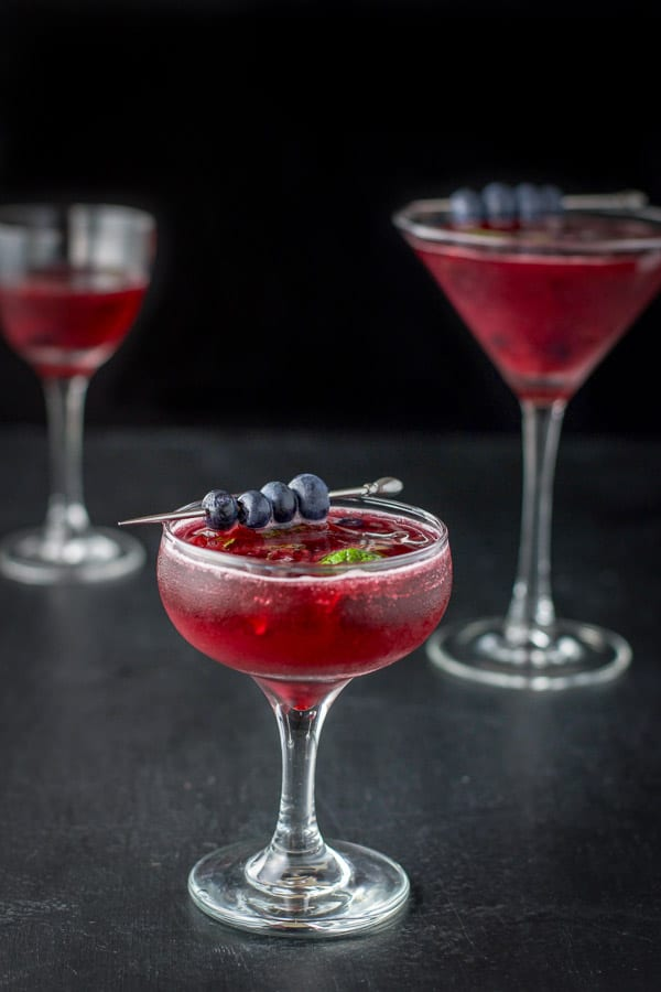 Blueberry cosmo with blueberries and mint leaves for garnish in a coupe glass in front and a martini glass in back