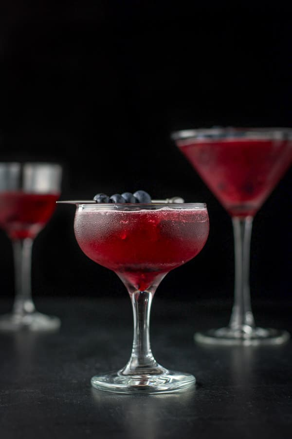 Vertical view of the blueberry cosmo with blueberries and mint leaves for garnish in a coupe glass in front and a martini glass in back