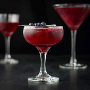 Three glasses of the blueberry cosmo in vertical view withe the coupe glass in front - square