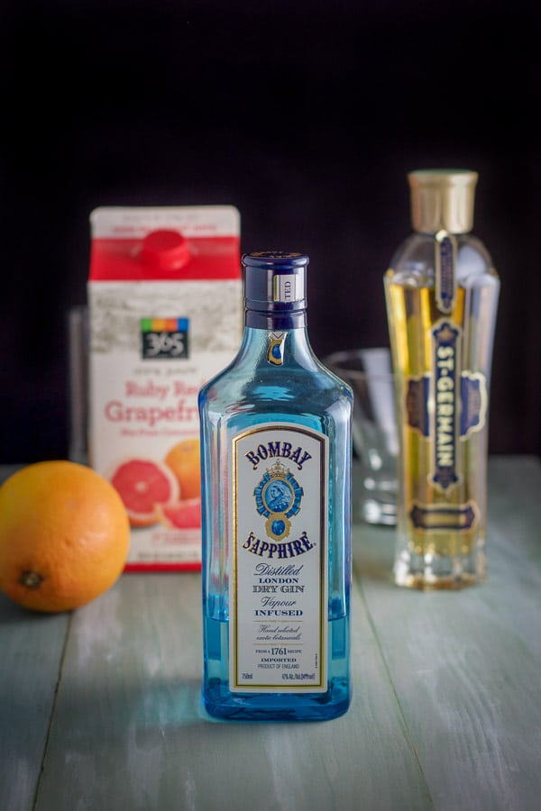 Gin, St. Germain liqueur and grapefruit on a green board