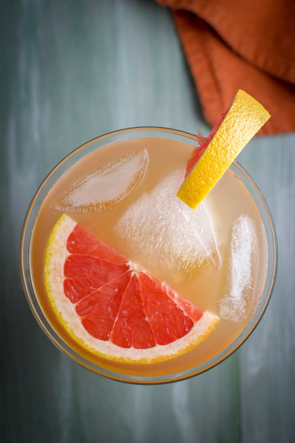 Overhead view of the pinkish Cocktail with a floating slice of grapefruit and another one on the rim of the glass