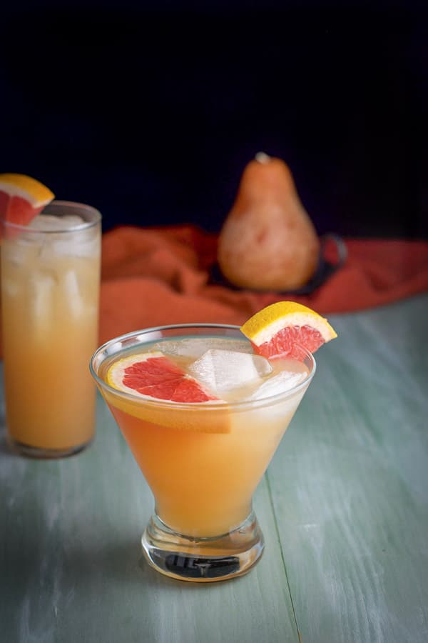 Short martini glass in front of the collins glass both filled with the Frenchie with a few slices of grapefruit in them