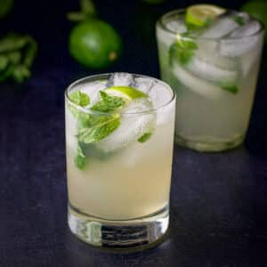 Double old fashioned glass filled with a minty and lime, rum drink - square