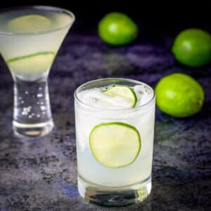 Two glasses filled with the vodka gimlet with whole limes in the background - square